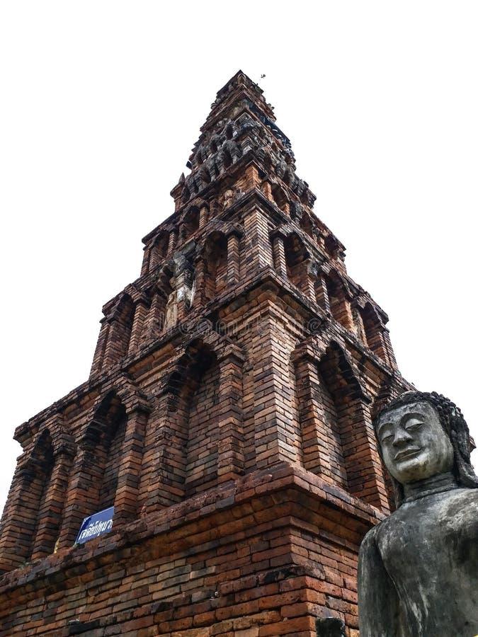 Ancient pagoda & Buddha. Ancient  pagoda named `Jedee Patumwadee` at Phrathathariphunchai temple in Thailand royalty free stock photos