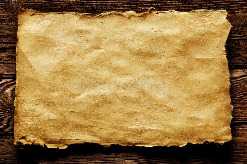 Ancient paper. An ancient paper with torn edges, on a brown wooden surface