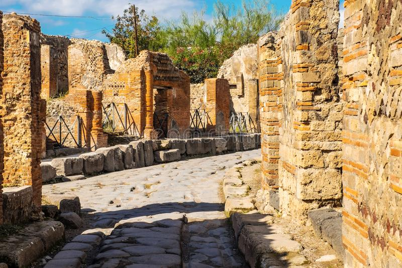 Ancient paved street is recovered in the middle of Roman ruins in Pompeii, Italy royalty free stock photos