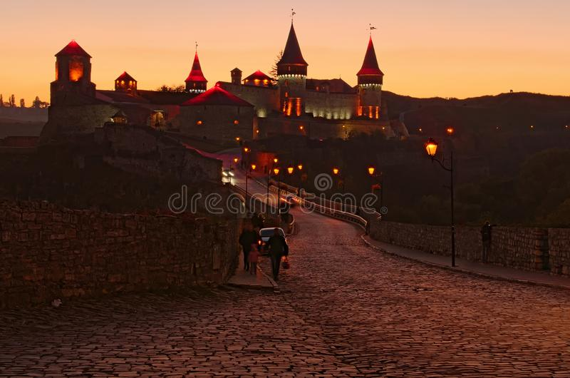 Ancient paving stone road with the bridge to the medieval Kamianets-Podilskyi castle. Autumn sunset landscape stock photos