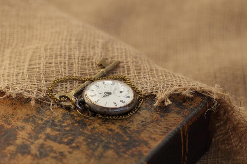 Ancient pocket watch and key on old folio half-covered with old sackcloth. Time passing concept. Knowledge eternity concept royalty free stock images