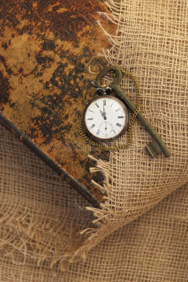 Ancient pocket watch and key on old folio half-covered with old sackcloth. Time passing concept. Knowledge eternity concept royalty free stock photography