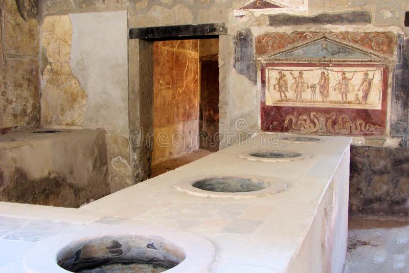 Ancient Pompeii restaurant with serving station. Ancient Pompeii - Thermopolium of Asellina with old food serving stations royalty free stock image