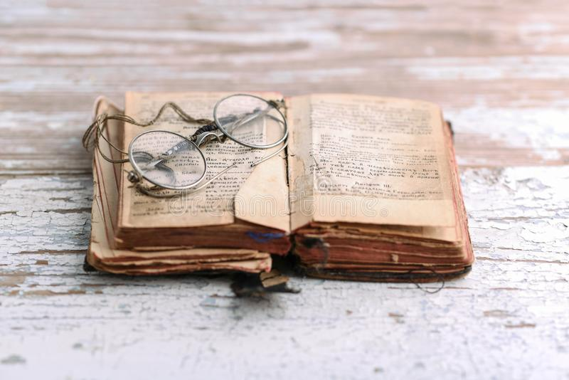 Ancient prayer book with old spectacles, Old Slavic language in the book. Ancient Christian prayer book with old spectacles, Old Slavic language in the book stock image