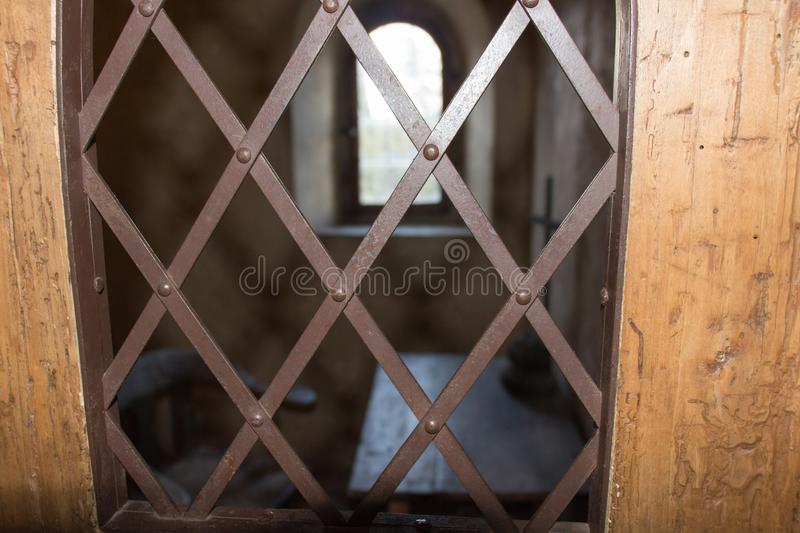 Ancient prison cell. View through a window with an iron grid. The view through a window with an iron grid on ancient prison cell royalty free stock images