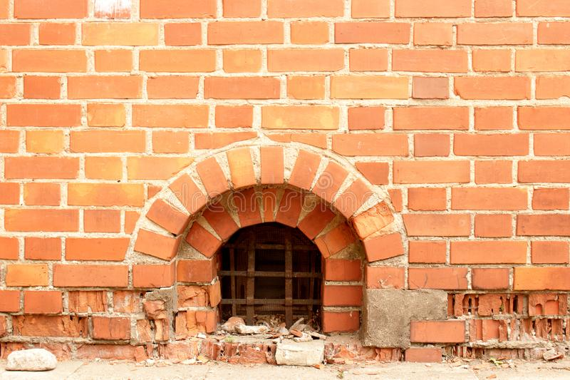 Ancient red brick wall with small cellar window with metal bars royalty free stock image