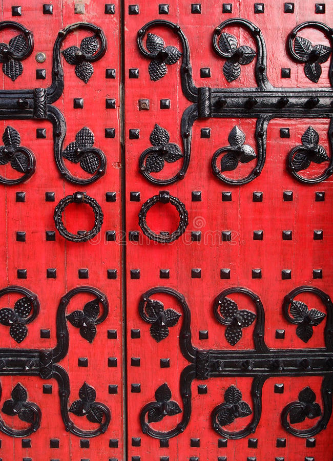 Ancient red doors with metal decorative design. Ancient red wooden doors with metal decorative design as flower/leave on it royalty free stock photography