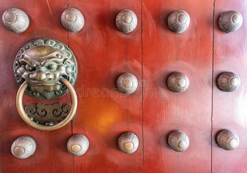 Ancient red wooden door decorated with bronze casting bas relief into Chinese lion face holding a ring-shaped handle in the mouth stock image