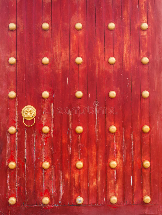 Ancient red wooden gate with lion door knocker royalty free stock images