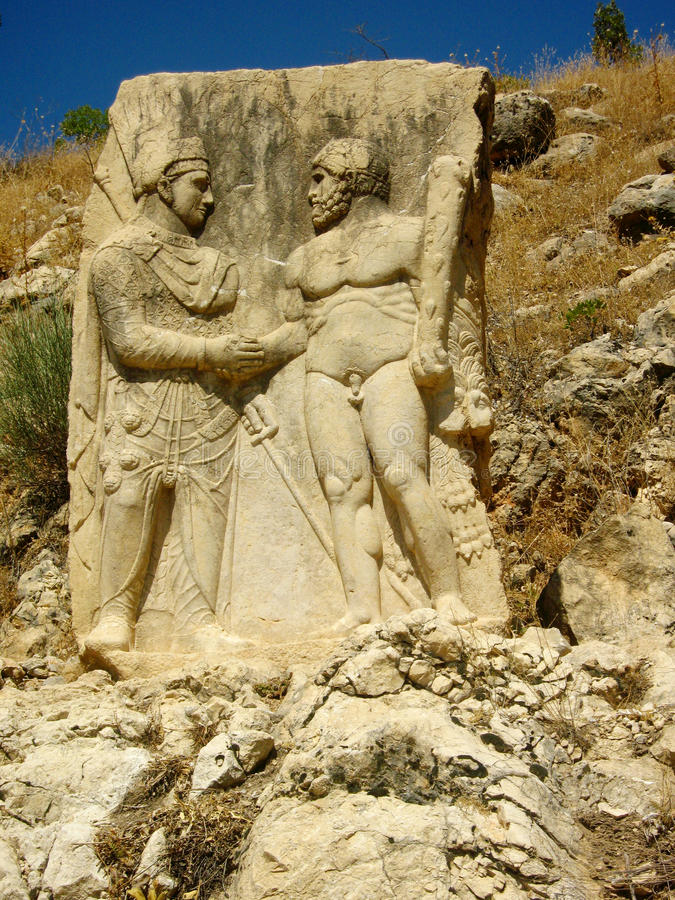 Ancient relief: Hercules shakes hands with King Antiochus. Turkey, Nemrut Dag National park royalty free stock photo