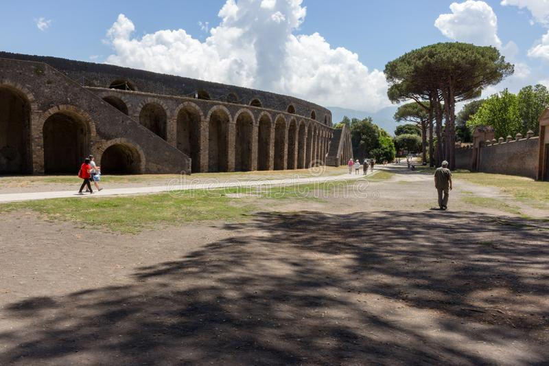Ancient roman amphitheatre exterior in Pompeii, Italy. Traditional antique colliseum and trees with shadows in Pompeii. royalty free stock photography