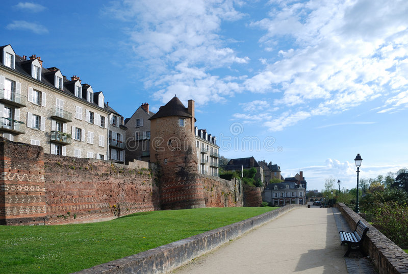 Ancient Roman boundary wall against modern Le Mans. Embankment of Le Mans with ancient Roman boundary wall against the spring sky and modern dwelling houses royalty free stock images