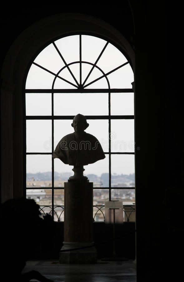 Ancient roman Papal bust statue. View of an ancient roman statue of a silhouetted Papal bust over a window, in the Vatican city royalty free stock image