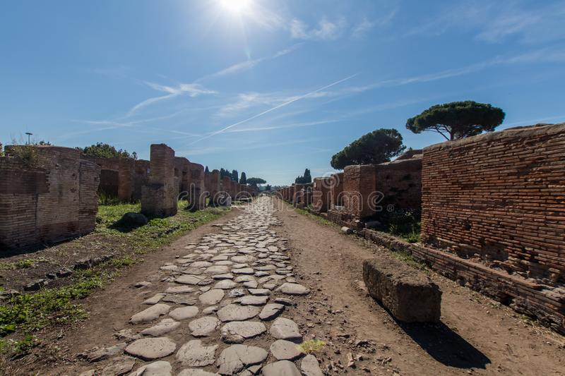 Ancient Roman road paved with stones for carriage. Decumano maxi. Mum in Ostia ancient 2nd century. Sun, sea pines and Roman ruins in the background royalty free stock photo