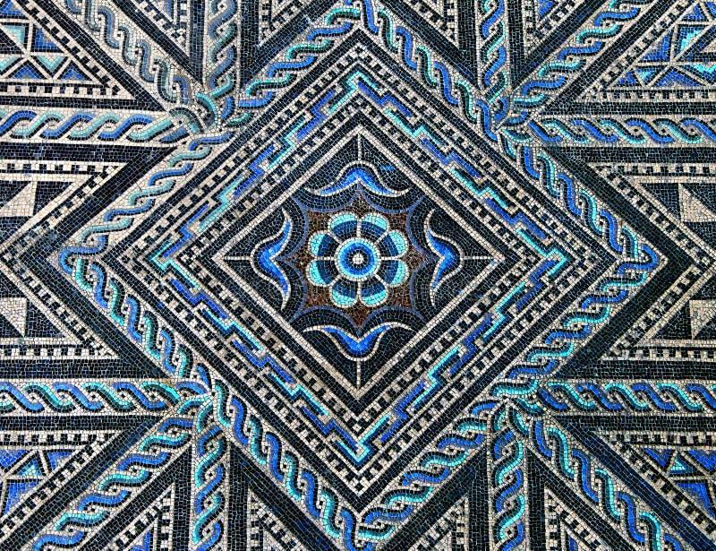 Ancient roman stone mosaic floor. Beautiful ancient roman stone mosaic floor with geometric and floral blue and black design stock image