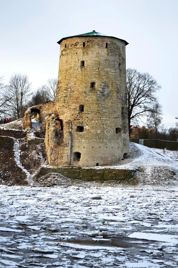 Ancient ruined tower by the river in winter, Russia, Pskov royalty free stock image