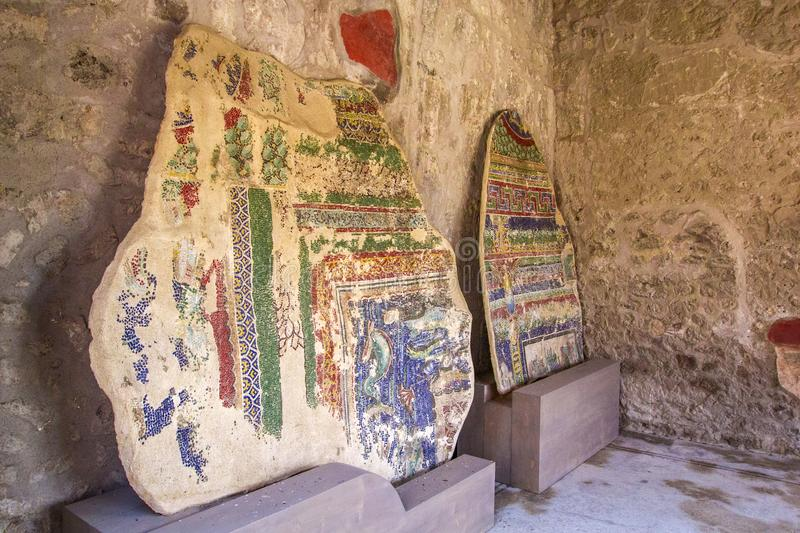 Part of the colored brick wall with painted frescoes in Pompeii, Naples, Italy. The ruins of the ancient city, excavations of Pomp stock photo