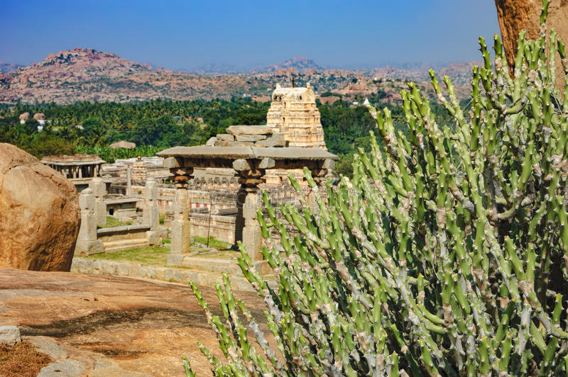 Ancient ruins and tropical plants in Hampi, India. Landscape with big stones - unique mountain formation with tropical plants and ancient ruins of city royalty free stock photo