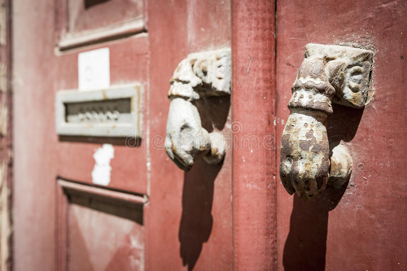 Ancient rusty door knockers and a mailbox on an ancient red wooden door. Two ancient rusty door knockers and a mailbox on an ancient red wooden door stock photo