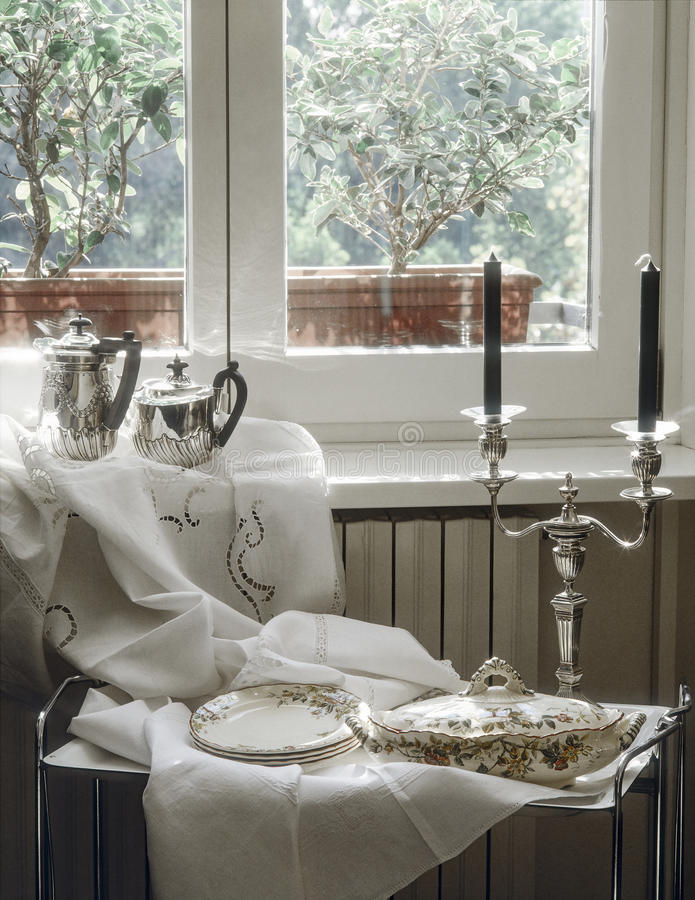 Ancient sauce boat, soup tureen and candelsticks. Near to window royalty free stock image
