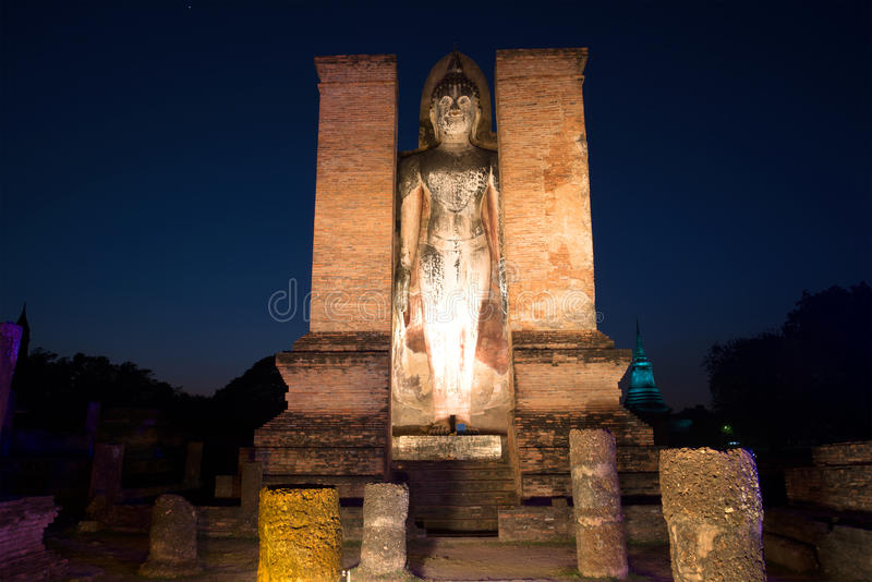 Ancient sculpture of standing Buddha in ruins of Wat Mahathat in lights for night illumination. Sukhothai, Thailand. Ancient sculpture of standing Buddha in stock photography