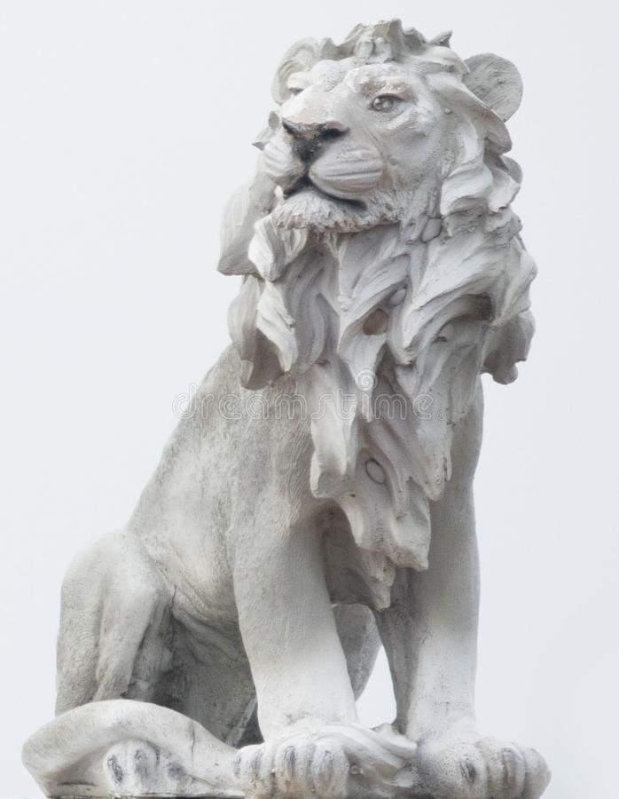 Ancient Sculpture of White sitting Coade stone Lion isolated on white backgrounds, clad strong statue, leadership symbol monument. Backgrounds royalty free stock image