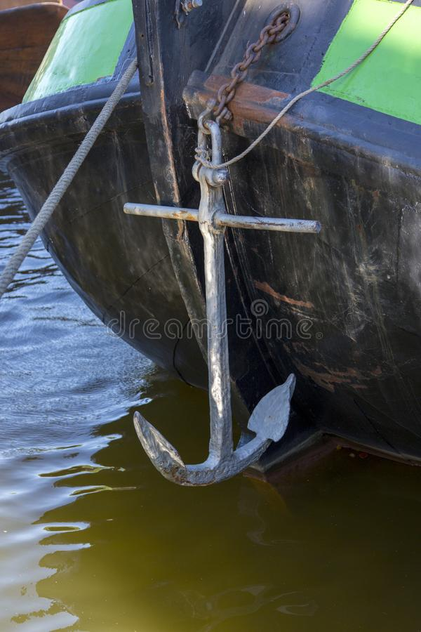 Ancient sea anchor aboard a boat on a chain.  stock photography
