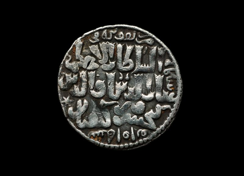 Ancient Seljuk silver coin with text on it isolated on black. Close-up shot, money, background, old, economy, rome, business, history, change, finance stock photos