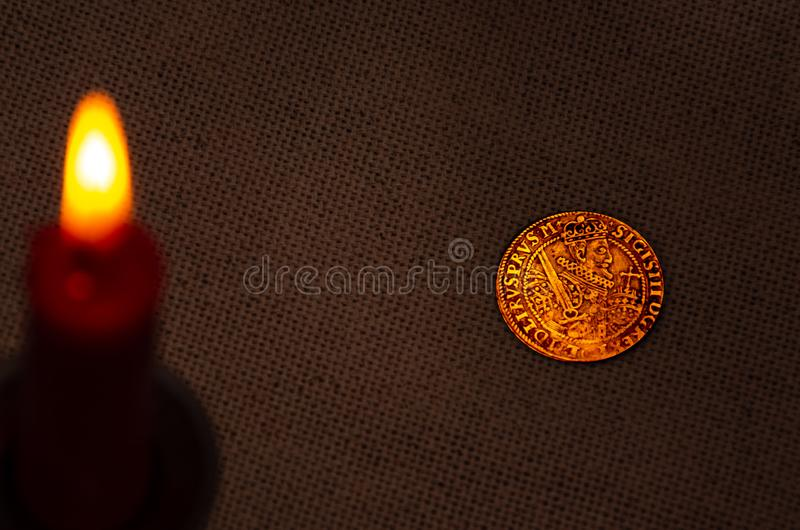 Ancient silver coin and burning candle royalty free stock photography