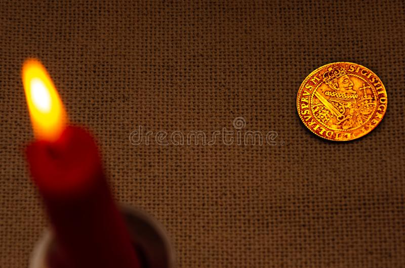 Ancient silver coin and burning candle royalty free stock photo