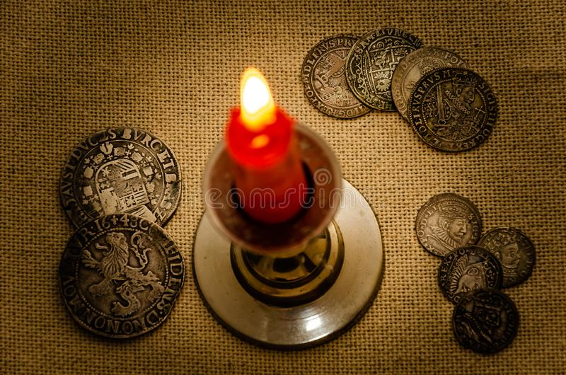 Ancient silver coins and burning candle royalty free stock photo