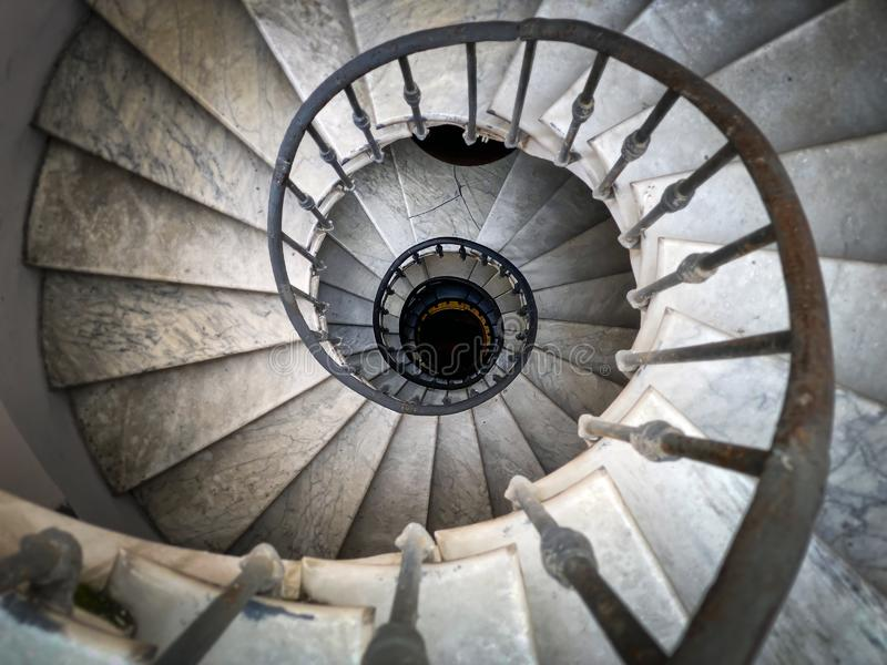 Ancient spiral staircase with decorated wrought iron handrails and marble steps inside an old palace in Rome stock photos