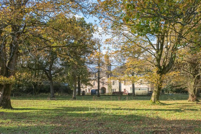 The Ancient Stables of Ardgowan at Autumn with its Spier Visable Through the Trees royalty free stock photography
