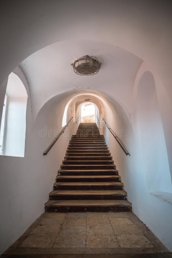 An old street staircase inside the tunnel leads up. There are stone steps. The walls of the tunnel are white with royalty free stock photo