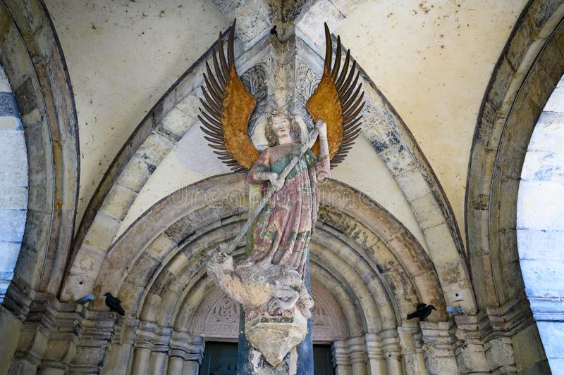 Archangel Michael on entrance portal of parish Church Saint Michael, Schwabisch Hall, Baden-Wuerttemberg, Germany. Ancient statue of Archangel Michael fighting stock image