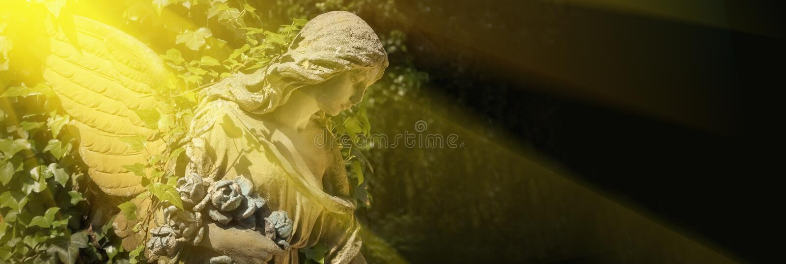 Ancient statue of gold angel with wings against dark background. Place for text for designer royalty free stock images