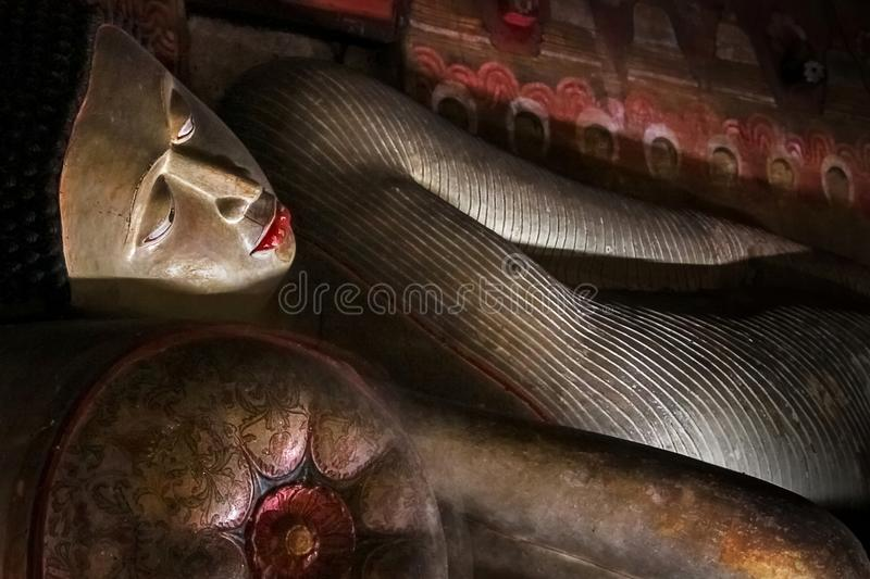 Ancient statue of a recumbent Buddha in the cave temple of Dambulla. Sri Lanka.  royalty free stock images