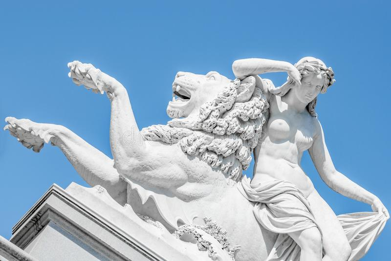 Ancient statue sensual renaissance era woman laying on big lion in Potsdam, Germany. Details, closeup stock image
