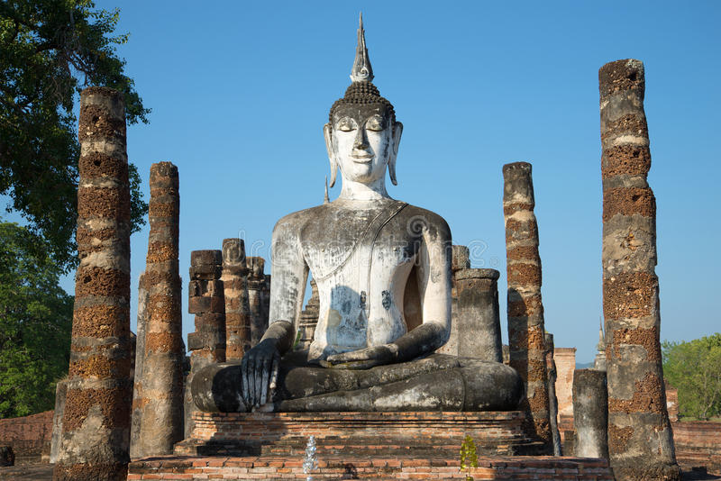 Ancient statue of a sitting Buddha. Ruins of the Buddhist temple Wat Mahathat in the Park of Sukhothai. Thailand stock photo