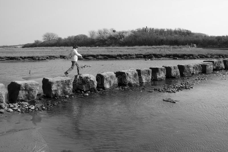 Ancient stepping stones. Woman crossing the Ancient stepping stones on the Isle of Anglesey North Wales royalty free stock photography