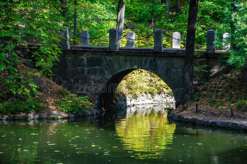 Ancient stone bridge with reflection in calm water surface of lake. Stone brick arch above pond. Landscape of Sofiyivka national park in Uman Ukraine. Autumn royalty free stock photos
