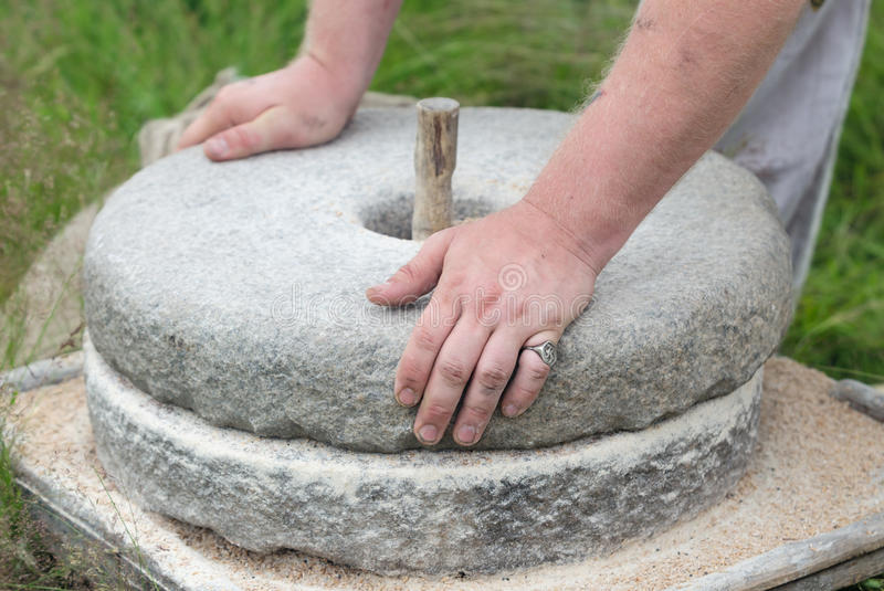 The ancient stone hand grain mill. Men`s hands rotate a stone millstone stock image