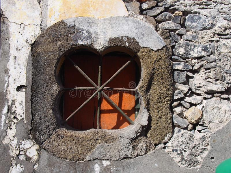 And ancient stone oblong shaped window with crossed bars with an orange shutter set in an old patched repaired grey wall with. Cracked cement stock photos