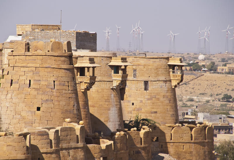 Ancient stone ramparts of Jaisalmer Fort. In Rajasthan, India. Line of wind mills used for generating power on the horizon stock images