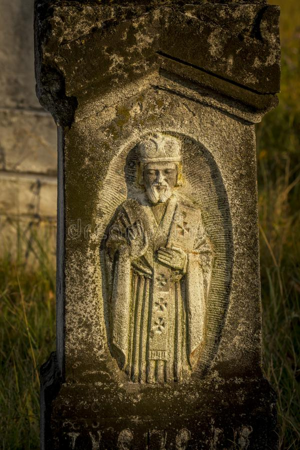 Ancient stone statue on Gothic graves at cemetery in Brody, Ukraine. An old abandoned overgrown cemetery. Traditional Catholic bur stock photo