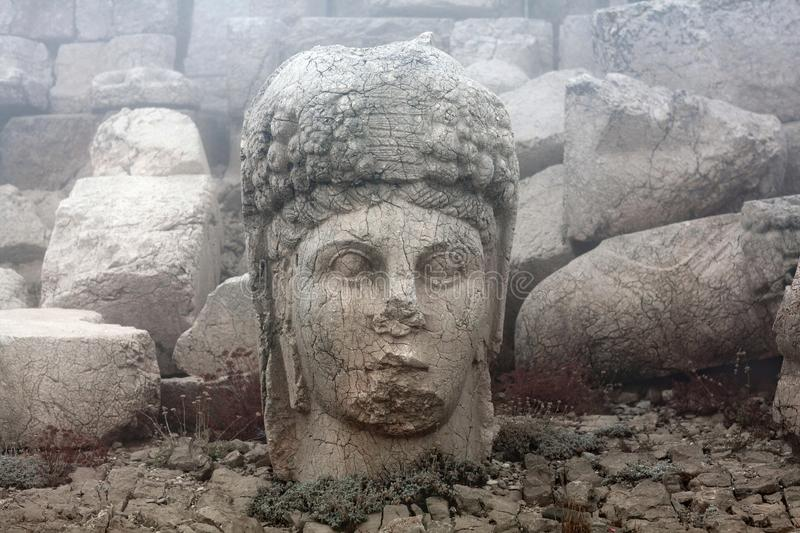 Statue of goddess of Commagene Tyche-Bakht on the top of Nemrut mount, Anatolia, Turkey. Ancient stone statue of goddess of Commagene Tyche-Bakht on the top of royalty free stock images