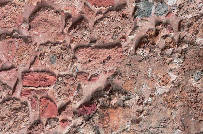 Ancient stone wall. Masonry of old red stones and bricks. Beautiful background. royalty free stock images