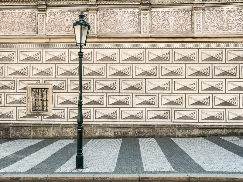 Ancient street lamp in front of a wonderful patterned house wall in Prague - Czech Republic royalty free stock photography
