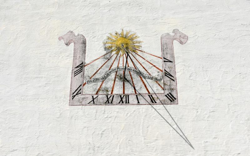 Ancient sundial on white wall at Wolfenschiessen in Switzerland stock photography