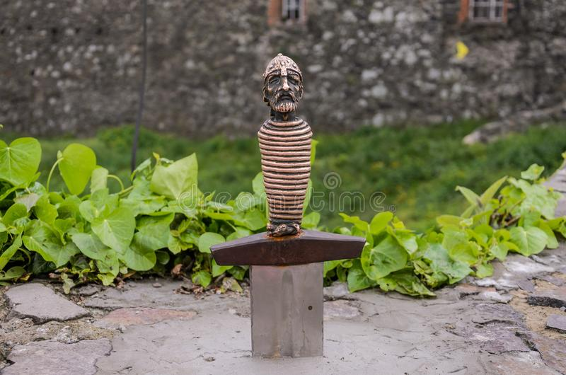 UZHGOROD, UKRAINE - MAY, 2019: Ancient sword in stone with a figure of a knight on the handle stock images